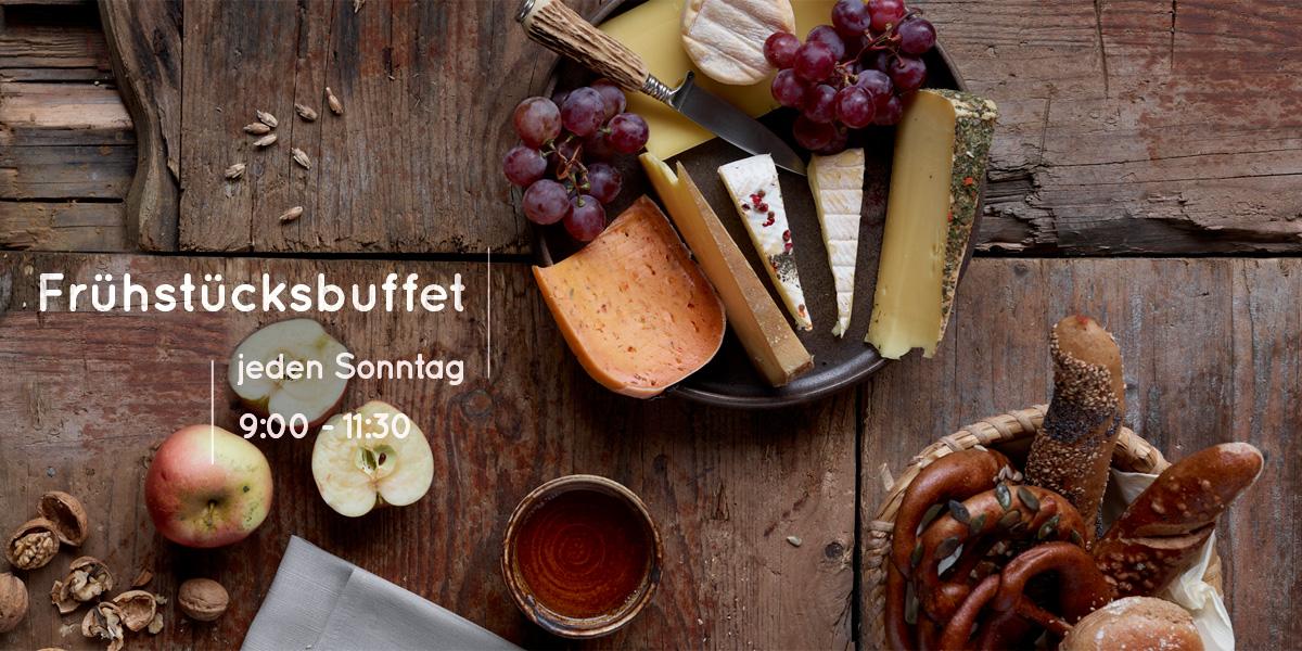 Frühstücksbuffet - jeden Sonntag - Brotkorb mit Käseplatte und Teetasse auf hölzernem Untergrund